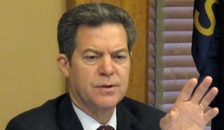 Kansas Gov. Sam Brownback asks a question during a meeting with legislative leaders about the state's plans for issuing $1 billion in bonds to boost the financial health of its public pension system for teachers and government workers, Thursday, July 2, 2015, at the Statehouse in Topeka, Kan. Market conditions could delay or prevent the state from issuing the bonds. (AP Photo/John Hanna)