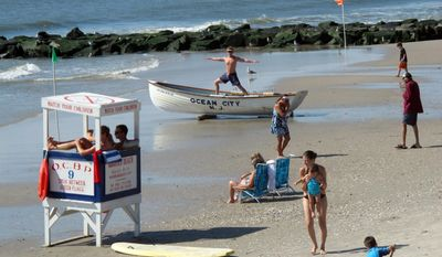 This Aug. 29, 2012 photo shows a lifeguard exercising atop a rowboat as people walk on the beach in Ocean City, N.J. Ocean City was named New Jersey's most popular beach on Thursday July 2, 2015, marking the second year in a row and third time overall that the southern New Jersey resort won an online voting competition. (AP Photo/Wayne Parry)