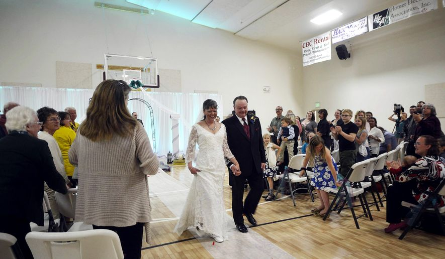 ADVANCE FOR SUNDAY, JULY 5 - In this Sunday June 28, 2015 photo, Bob and Hope Hensler walk down the aisle during their wedding ceremony in Sterling, Alaska. The Card Street fire burned through more than 8,000 acres of land since it began June 15. One of those buildings was the home of the Hensler's, who after a 14-year engagement, were married at the Sterling Community Center. (Megan Pacer/Peninsula Clarion via AP) MANDATORY CREDIT