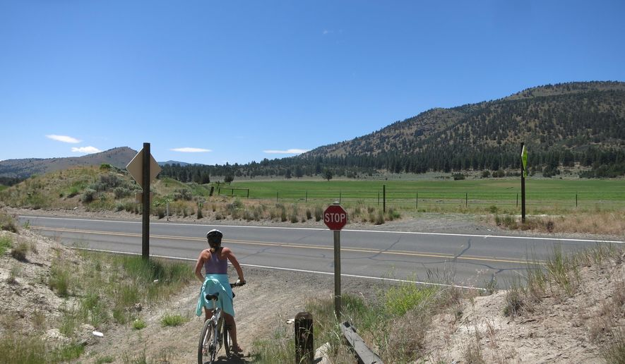 In this June 21, 2015 photo, a mountain biker checks for traffic on Highway 140 near the rural Klamath County community of Olene in Oregon. The bike trail slices through a canyon carved decades ago by crews that built the OC&E line, a logging railroad between Klamath Falls and Bly. (Lee Juillerat/The Herald And News via AP)