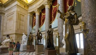 A statue of missionary Junipero Serra, right, is seen in Statuary Hall, also known as the Old Hall of the House, on Capitol Hill in Washington, Thursday, July 2, 2015. California lawmakers are shelving a plan to replace the statue with astronaut Sally Ride, bowing to pressure to drop the idea until after Pope Francis's September visit to the U.S., when he plans to make the 18th-century missionary a saint. (AP Photo/Pablo Martinez Monsivais) ** FILE **
