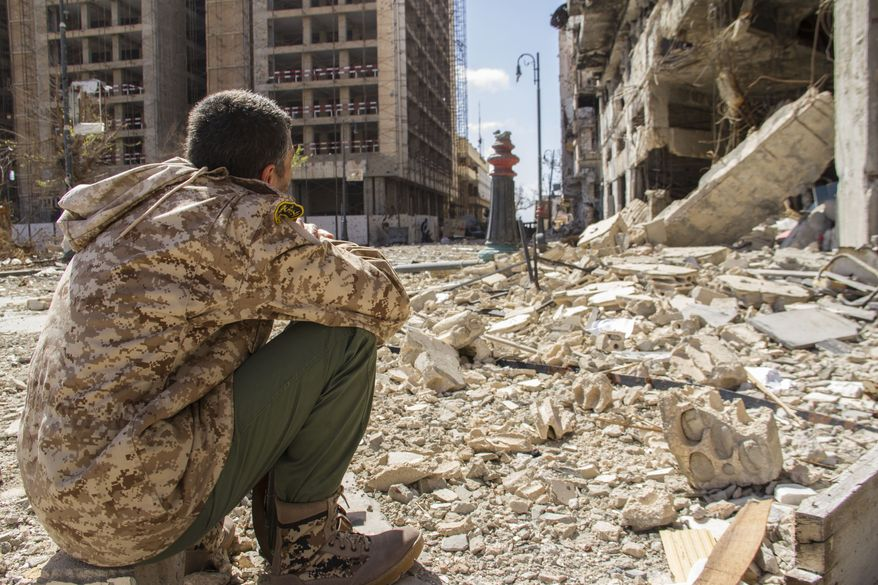 In this photo taken on April 4, 2015, a man looks on at the destruction on a street of the city of Benghazi, Libya. Destruction has permeated the North African country since the civil war ousted Moammar Gadhafi four years ago. For Benghazi, the past year was the worst. (AP Photo/Mohamed Salama)