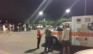 Emergency personnel stand by as evacuees gather at the Foothills Mall early Thursday, July 2, 2015, in Maryville, Tenn., after they were forced to leave their homes when rail car carrying a flammable and toxic gas derailed and caught fire. (Brittany Bade/WBIR.com via AP)