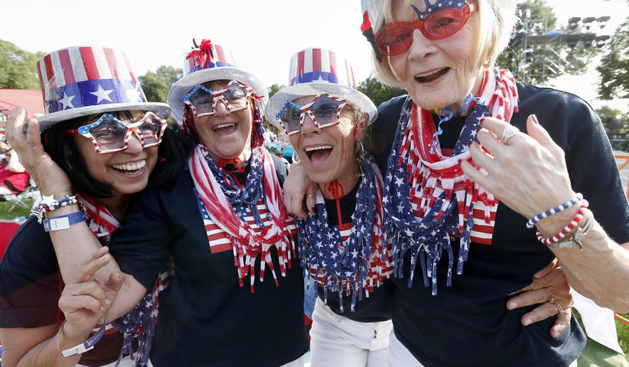 Fom left to right, spectators Mary Ann Rollings, Gloria Kelley, Linda Stacey and Eileen Bitter pose for a photo before rehearsal for the annual Boston Pops orchestra Fourth of July concert on the Esplanade in Boston, Friday, July 3, 2015. (AP Photo/Michael Dwyer)