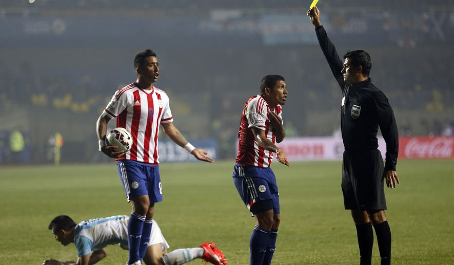 Referee Sandro Ricci, from Brazil, shows a yellow card to Paraguay's Richard Ortiz after he fouled Argentina's Sergio Aguero (right) during a Copa America semifinal soccer match at the Ester Roa Rebolledo Stadium in Concepcion, Chile, on June 30, 2015. South American players are known for their vivid complaints and have long enjoyed more leeway when interacting with referees, especially compared to leagues in Europe, and now Brazil wants to put an end to that. (Associated Press) **FILE**