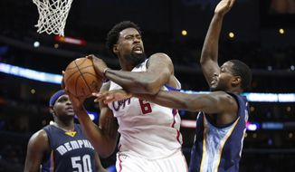 FILE - In this Saturday, April 11, 2015 file photo, Los Angeles Clippers' DeAndre Jordan brings in a rebound in front of Memphis Grizzlies' Zach Randolph, left, and JaMychal Green, right, during the second half of an NBA basketball game in Los Angeles. DeAndre Jordan has chosen the Mavericks over the Los Angeles Clippers in what turned into a tense boom-or-bust wait for Dallas in pursuit of the free-agent center. Two people familiar with the deal tell The Associated Press that Jordan agreed to terms Friday, July 3, 2015. (AP Photo/Danny Moloshok, File)