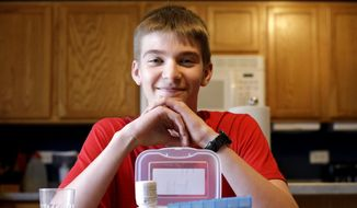 In this photo taken Wednesday, May 13, 2015, Hayden Murphy, 13, sits for a photo with his medicine at his home in Plainfield, Ill. Hayden is among more than 400 children and adults participating in U.S. government-funded international research investigating whether experimental insulin capsules can prevent or at least delay Type 1 diabetes. (AP Photo/Nam Y. Huh)