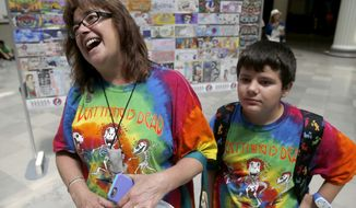 In this Tuesday, June 30, 2015, photo, Rebecca Ostrega, from Oswego, Ill., talks about her devotion to the Grateful Dead as she and her son Jake, visit an exhibit dedicated to the band at the Field Museum in Chicago. The Dead are scheduled to perform multiple shows over the July 4th weekend at Soldier Field. (AP Photo/Charles Rex Arbogast)