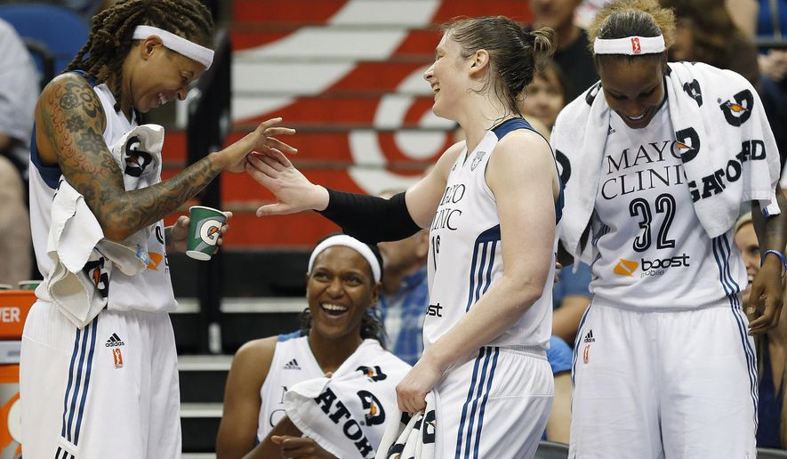 Minnesota Lynx guard Seimone Augustus, left, celebrates with teammate guard Lindsay Whalen (13) during the second half of a WNBA basketball game against the Seattle Storm, Friday, July 3, 2015, in Minneapolis. The Lynx won 82-57. (AP Photo/Stacy Bengs)