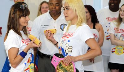 Brooklyn Borough President Eric Adams watches Michelle Lesco, left, and Miki Sudo, right, during a news conference to promote the upcoming Nathan's Famous Fourth of July Hot-Dog Eating Contest, Friday, July 3, 2015, at Brooklyn Borough Hall in New York.  (AP Photo/Frank Franklin II)