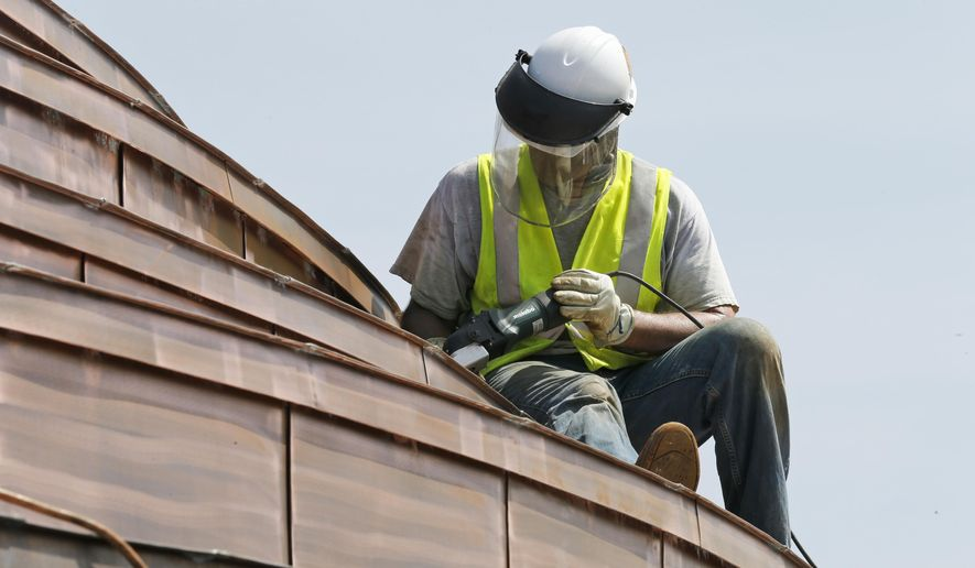 In this June 23, 2015 photo, a worker polishes the copper roof of the Rotunda at the University of Virginia in preparation for painting in Charlottesville, Va. The centerpiece of the university's historic Grounds, built from 1822 to 1826, is the focus of a $52 million renovation.  (AP Photo/Steve Helber)