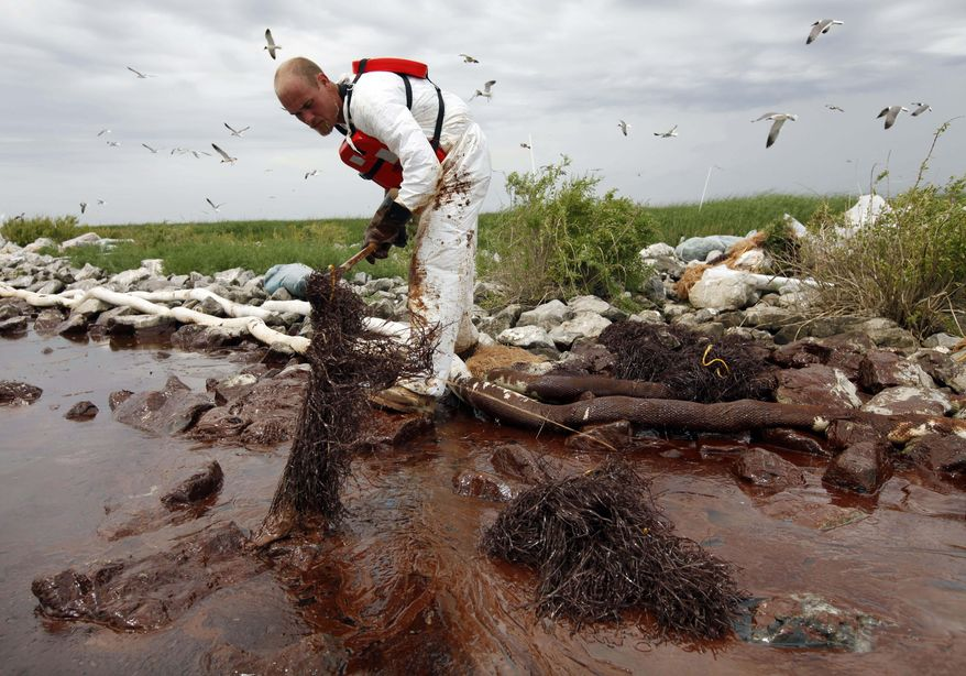 FILE- In this June 4, 2010 file photo, a worker picks up blobs of oil with absorbent snare on Queen Bess Island at the mouth of Barataria Bay near the Gulf of Mexico in Plaquemines Parish, La. BP and five Gulf states announced a record $18.7 billion settlement Thursday, July 2, 2015,  that resolves years of legal fighting over the environmental and economic damage done by the energy giant's oil spill in 2010. (AP Photo/Gerald Herbert, File)