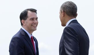President Barack Obama is greeted by Wisconsin Gov. Scott Walker as he arrives on Air Force One at La Crosse Regional Airport, Thursday, July 2, 2015, in La Crosse, Wis. The president is en route to the University of Wisconsin at La Crosse where he is to speak about the economy and promote a proposed Labor Department rule that would make more workers eligible for overtime. (AP Photo/Carolyn Kaster)