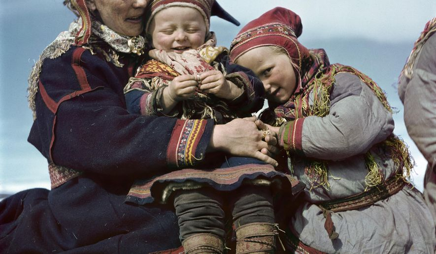 The 1951 photo by Robert Capa provided by the International Center of Photography/Magnum Photos shows a Lapp family in Norway.  Rarely seen color photographs by Robert Capa, born Endre Friedmann, the legendary Hungarian photographer best known for his battlefield pictures from the Spanish Civil War and World War II, especially D-Day, are being shown for the first time in Europe at the Budapest institution which bears his name.  (Robert Capa/International Center of Photography/Magnum Photos via AP)