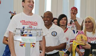 Brooklyn Borough President Eric Adams watches as Joey Chestnut, left, weighs in during a news conference to promote the upcoming Nathan's Famous Fourth of July Hot-Dog Eating Contest, Friday, July 3, 2015, at Brooklyn Borough Hall in New York.  (AP Photo/Frank Franklin II)