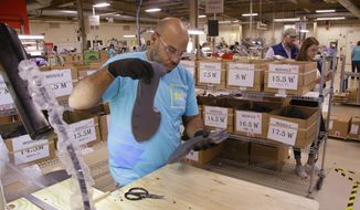 In this photo taken Wednesday, July 1, 2015, Loyd Johnson inspects a newly formed pair of midsoles for the New Balance proposed 950v2 sneaker, that has passed military testing, before placing them in their sizing box at one of company's manufacturing facilities in Boston. New Balance is pressing the Pentagon to buy American-made footwear for the troops instead of sneakers from rival Nike that are made in China. (AP Photo/Stephan Savoia)