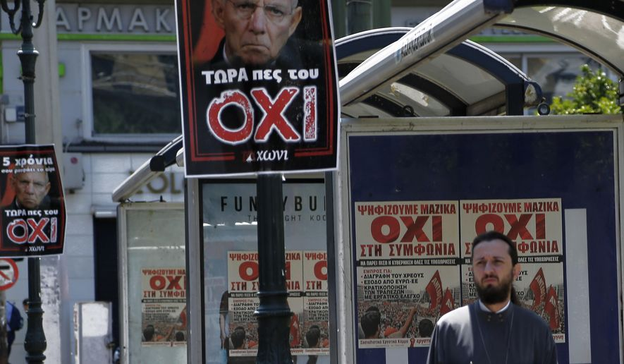 """A Greek Orthodox priest walks by the poster of """"NO"""" and posters depicting German Finance Minister Wolfgang Schaeuble, top center,  reading ''For five years he is drinking your blood, now tell him NO'' referring to the upcoming referendum in central Athens, on Friday, July 3, 2015. (AP Photo/Petros Karadjias)"""