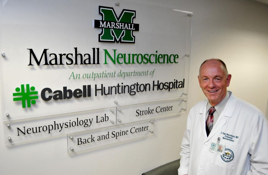 In this photo taken on Wednesday, June 17, 2015, Dr. Paul Muizelaar poses in the Marshall University Neuroscience department located a Cabell Huntington Hospital in Huntington, W.Va. Marshall University has recruited the noted surgeon who ran into trouble experimenting with human brains using bowel bacteria but will continue the same research on rats under tight restrictions. (AP Photo/Chris Tilley)