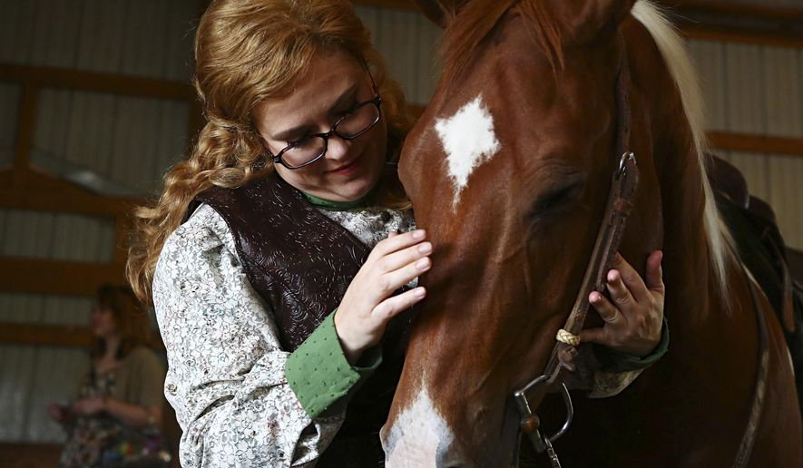 """ADVANCE FOR WEEKEND EDITIONS JULY 4-5 - In this June 18, 2015 photo, Opera singer, Alexandra """"Lexi"""" Lobianco pets Romeo before riding him at a stable in Prole, Iowa. When the white-maned, copper-splotched Romeo made his operatic debut last month, the second night of the company's new season, he briefly stole the scene from the leading lady who rode him. And she is OK with that: It's part of the fun of performing with real animals. (Brian Powers/The Des Moines Register via AP)  MAGS OUT, TV OUT, NO SALES, MANDATORY CREDIT"""