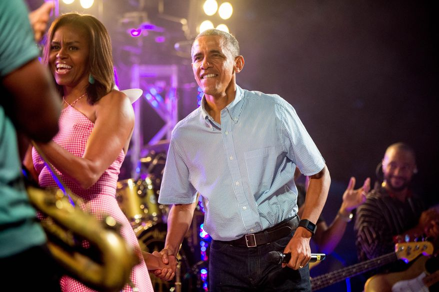 President Barack Obama, accompanied by first lady Michelle Obama, left, arrives to deliver remarks during an Independence Day celebration on the South Lawn at the White House in Washington, Saturday, July 4, 2015. (AP Photo/Andrew Harnik)