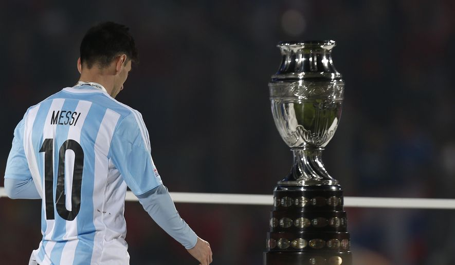 Argentina's Lionel Messi walks by the Copa America trophy after receiving the silver medal after the final game with Chile at the National Stadium in Santiago, Chile, Saturday, July 4, 2015. Chile goalkeeper Claudio Bravo made a save and striker Alexis Sanchez converted the winning penalty as host Chile defeated Argentina 4-1 in a shootout after a 0-0 draw in the Copa America final. (AP Photo/Luis Hidalgo)