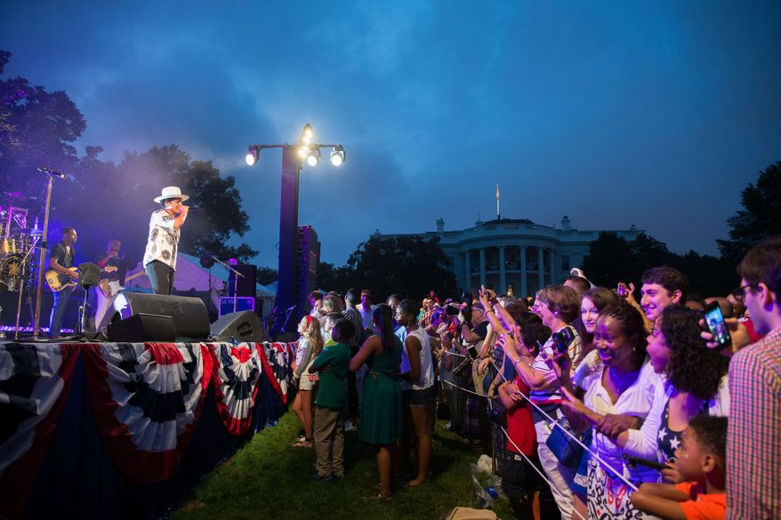 Bruno Mars, left, welcomes President Barack Obama to the stage during an Independence Day celebration on the South Lawn at the White House in Washington, Saturday, July 4, 2015. (AP Photo/Andrew Harnik)