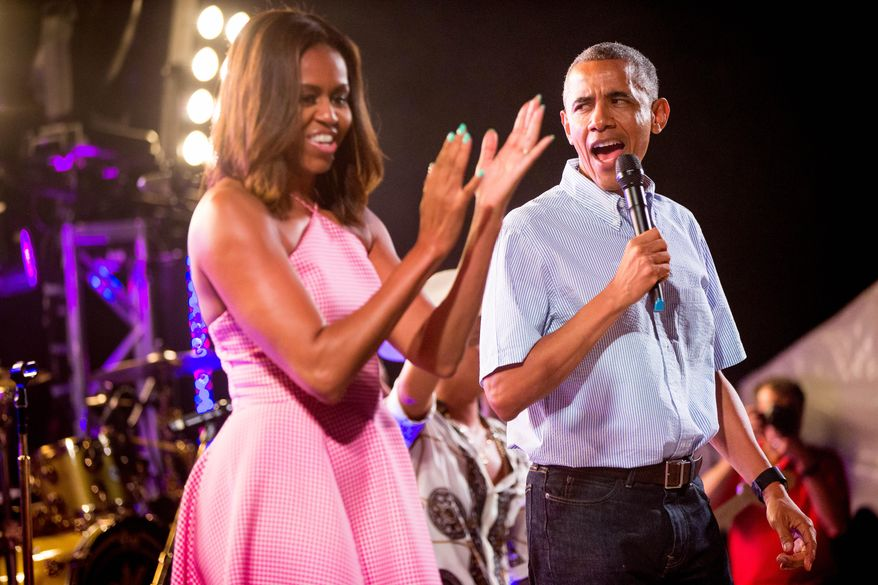 President Barack Obama, accompanied by first lady Michelle Obama, left, speaks during an Independence Day celebration on the South Lawn at the White House in Washington, Saturday, July 4, 2015. (AP Photo/Andrew Harnik)