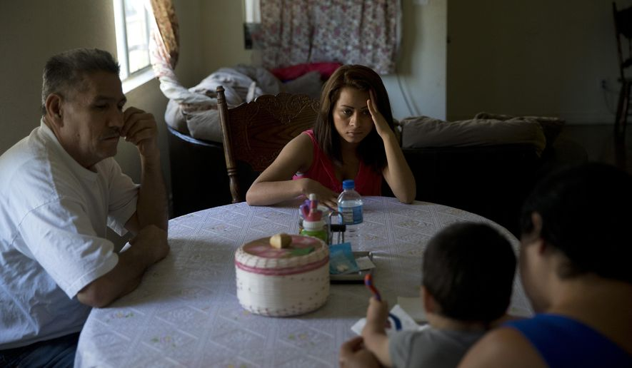 In this Monday, June 8, 2015 photo, 18-year-old Dunia Bueso, center, and her relative, Augustin Vargas, left, look at Bueso's 1-year-old son, Joshua Tinoco, foreground, sitting on the lap of Martina Perez, at their home in Los Angeles. At a brief hearing, a government lawyer tells the teenage mother that her son is an immigration enforcement priority for the United States and should be sent back to his native Honduras even though she is being allowed to stay and seek a green card. (AP Photo/Jae C. Hong)