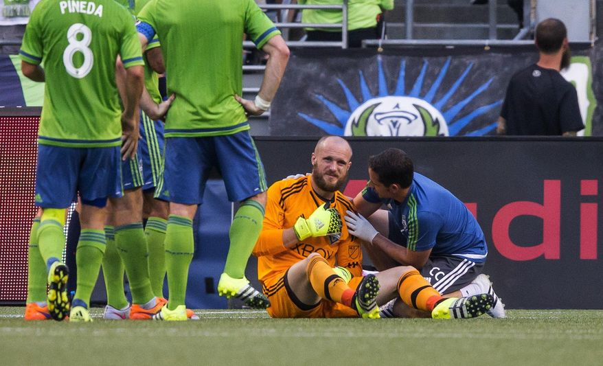 A trainer looks at the shoulder of Seattle Sounders keeper Stefan Frei, who was injured in a collision during the first half against D,C, United in an MLS soccer game Friday, July 3, 2015, in Seattle. (Den Rutz/The Seattle Times via AP)