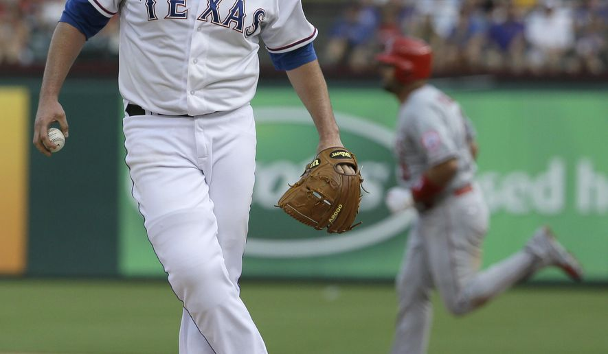 Texas Rangers starting pitcher Colby Lewis, left, kicks the mound as Los Angeles Angels Albert Pujols runs the bases after his solo home run during the fourth inning of a baseball game in Arlington, Texas, Sunday, July 5, 2015. (AP Photo/LM Otero)