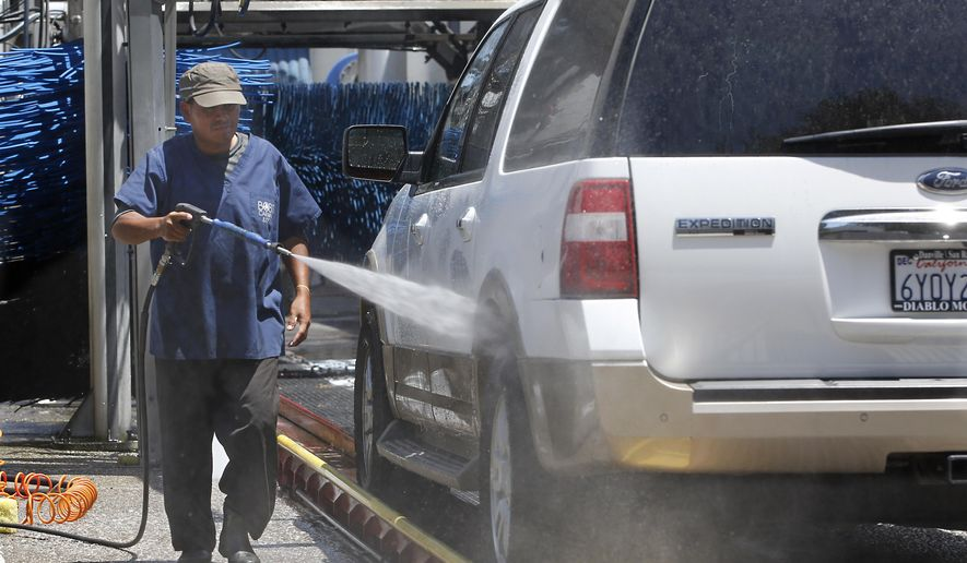 "In this photo taken Wednesday, June 24, 2015, Maximinio Gonzales washes a car at Bob's Car Wash in Roseville, Calif. To reduce water use, owner Nancy van Overbeek says they have upgraded their recycling and reclamation system and are not watering their lawn. Overbeek has noticed the drought surcharge on her water bill, but hasn't had to pass it along to customers because of the slight reduction in the primary water bill. Californians who thought their water bills would be reduced as they conserve water have found local water agencies are charging more for water and charging ""drought surcharges"" to make up  lost revenue.(AP Photo/Rich Pedroncelli)"