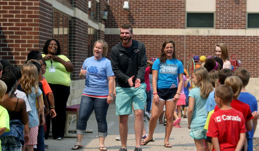 In this photo taken on Tuesday, June 30, 2015, Christopher Kurt, center, Aldo Leopold Middle School music teacher, jokes and cheers with the students bringing them in from recess, along with Shalee Brown, a North Hill Elementary School associate top right, Lynette Van Scoy, Sunnyside Elementary School teacher, and Mary Roundy, 16, a volunteer from Notre Dame High School, during summer school at Grimes Elementary School in Burlington, Iowa. The classes meet until August 10. (John Gaines/The Hawk Eye via AP) MANDATORY CREDIT