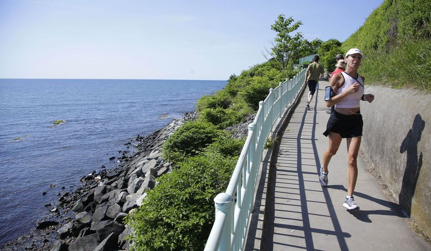 FILE - In this June 24, 2014 file photo, a runner and walkers travel along the Newport Cliff Walk, in Newport, R.I.  The three-and-a-half mile walkway that borders the shore line, is now smoke-free. The city council voted June 10 in favor of an ordinance that banned smoking on city beaches, in the park and on the Cliff Walk.  (AP Photo Stephan Savoia, File)