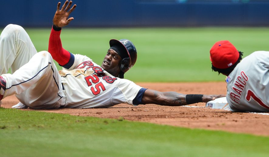 Atlanta Braves center fielder Cameron Maybin (25) reacts after diving safelyback to third base as Philadelphia Phillies third baseman Maikel Franco (7) is unable to make the tag in the first inning of a baseball game Sunday, July 5, 2015, in Atlanta. Maybin was advancing to third from second base on a single hit by Braves' A.J. Pierzynski. (AP Photo/Jon Barash)
