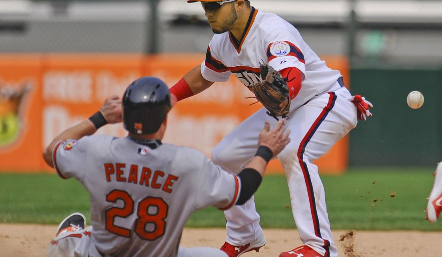 Baltimore Orioles' Steve Pearce, left, slides safely under the glove of Chicago White Sox's Carlos Sanchez, right, during the seventh inning of a baseball game in Chicago on Sunday, July 5, 2015. (AP Photo/Matt Marton)