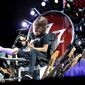 """The Foo Fighters' Dave Grohl performs from a throne of his own making, after breaking his leg during a show in Sweden. A specially designed gurney allowed Mr. Grohl's chair to extend onto a catwalk to get him closer to the crowd, sometimes with bandmates joining him. """"There was no way I was canceling this concert,"""" Mr. Grohl told the enthusiastic crowd. (Associated Press photographs)"""
