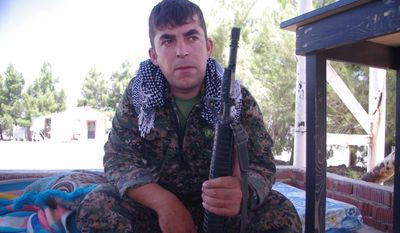 """A Kurdish YPG fighter at a base in northeastern Syria said his M-16 assault rifle, stamped with the words """"Property of U.S. Govt,"""" was captured from the Islamic State, which probably took it from the Iraqi army. (Campbell MacDiarmid/Special to The Washington Times)"""