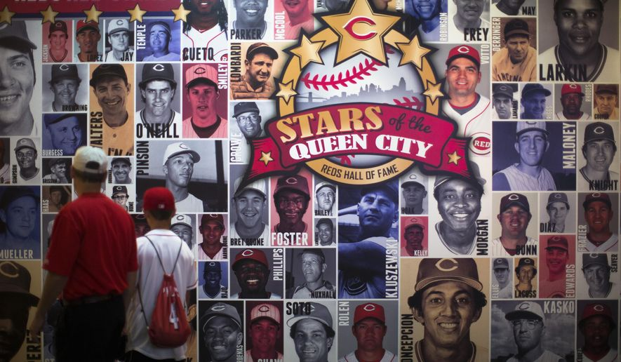 """Visitors browse the """"Stars of the Queen City"""" exhibit at the Cincinnati Reds Hall of Fame and Museum, Friday, July 3, 2015, in Cincinnati. Adjacent to the Great American Ball Park, where the July 14 All-Star Game will be played, the Reds' own Hall of Fame and Museum is filled with artifacts and interactive exhibits covering Cincinnati players from the Wrights to the """"Big Red Machine"""" of the 1970s to the current team. (AP Photo/John Minchillo)"""
