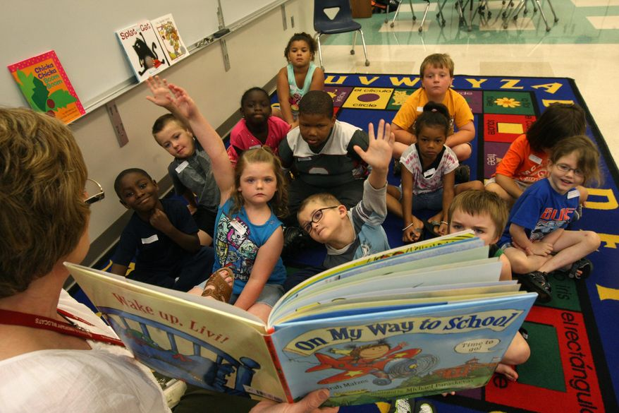 "In this file photo taken on Tuesday, June 30, 2015, Heidi Torrance, a teacher at Sunnyside Elementary School, reads ""On My Way to School"" and interacts with students going into first grade during summer school at Grimes Elementary School in Burlington, Iowa. The class helps the students maintain the skill levels so they are prepared for school in the fall. The classes meet until August 10.  (John Gaines/The Hawk Eye via AP) MANDATORY CREDIT"