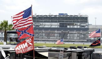 Confederate and American flags fly on top of motor homes at Daytona International Speedway, Saturday, July 4, 2015, in Daytona Beach, Fla. NASCAR and the speedway offered to replace any flag a race brings to the track with an American flag. (AP Photo/Phelan M. Ebenhack)