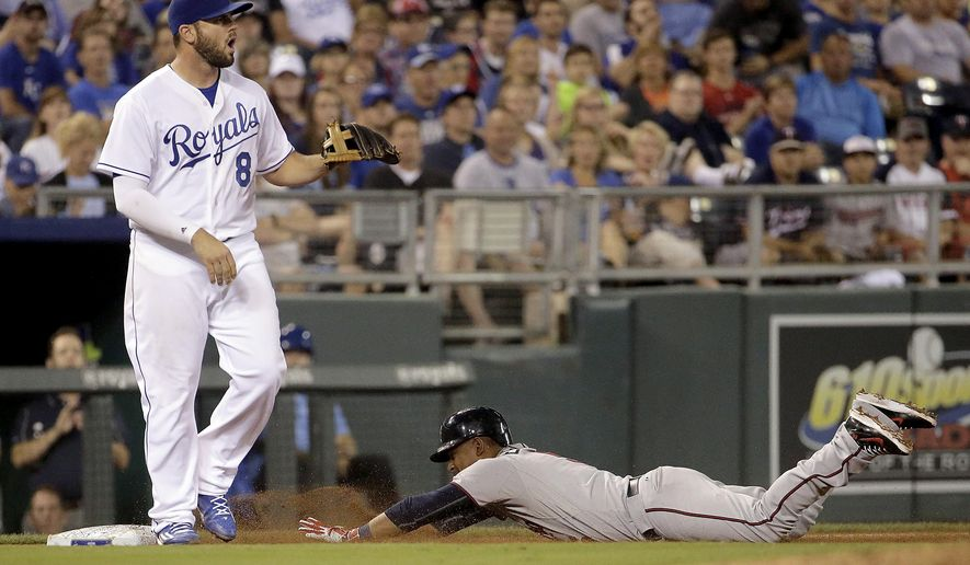 Minnesota Twins' Eduardo Escobar slides in with an RBI triple as Kansas City Royals third baseman Mike Moustakas waits for the ball during the ninth inning of a baseball game against the Kansas City Royals Thursday, July 2, 2015, in Kansas City, Mo. (AP Photo/Charlie Riedel)