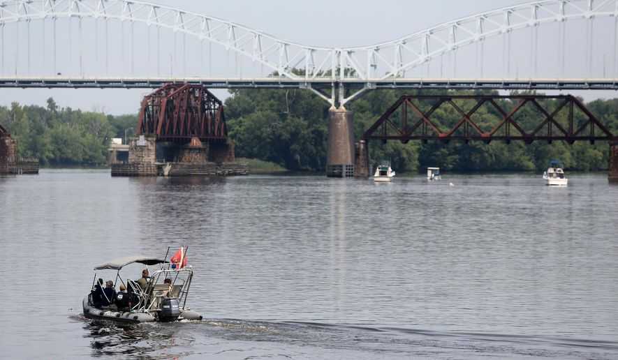Authorities search the Connecticut River near the Arrigoni Bridge for a missing child, Monday, July 6, 2015, in Middletown, Conn. Police issued an alert Monday for 7-month-old Aaden Moreno, who may have been with his father when the man jumped from the Arrigoni Bridge Sunday night. (Lauren Schneiderman/The Hartford Courant via AP)