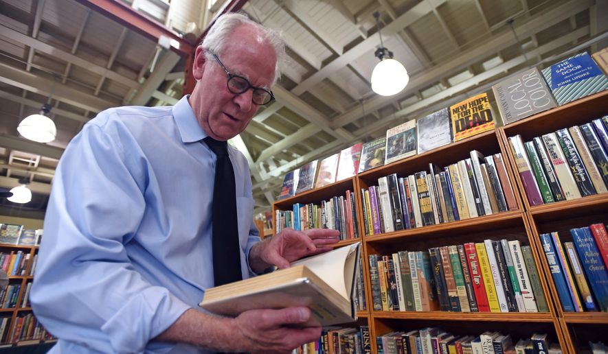 FOR RELEASE MONDAY, JULY 13, 2015, AT 12:01 A.M. CDT.- Patrick Coleman, curator of books for the Minnesota Historical Society, searches for books of historical value during the Antiquarian Book Fair at the Minnesota State Fairgrounds in Falcon Heights, Minn. on Friday, June 26, 2015. For more than 35 years, the self-described book geek, history nut and lover of Minnesota has collected thousands of books, maps and documents for the historical society's massive collection. (Holly Peterson/The St. Paul Pioneer Press via AP)