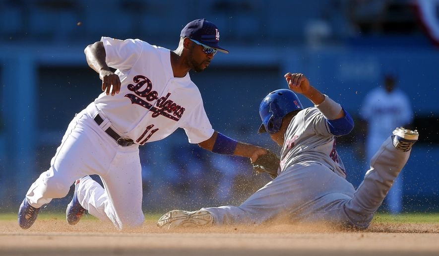 New York Mets' Juan Lagares, right, is tagged out by Los Angeles Dodgers shortstop Jimmy Rollins while trying to steal second base during the fifth inning of a baseball game, Saturday, July 4, 2015, in Los Angeles. (AP Photo/Mark J. Terrill)