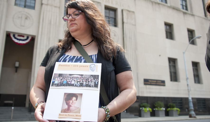 Liz Lupo, of Lake Orion, Mich., holds a sign memorializing her mother, who died while under Dr. Fata's care, outside the federal courthouse in downtown Detroit, Monday July 6, 2015. Fata is headed to prison for fraud and other crimes. But U.S. District Judge Paul Borman first is hearing from experts and former patients about the extent of his scheme to reap millions of dollars from Medicare and other health programs. (David Guralnick/Detroit News via AP)  DETROIT FREE PRESS OUT; HUFFINGTON POST OUT; MANDATORY CREDIT