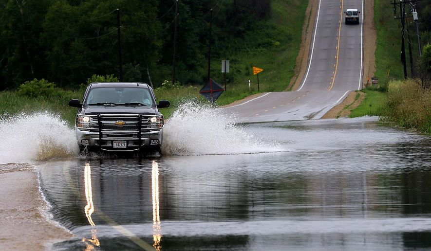 A vehicle drives through flood waters on Highway 170, Monday, July 6, 2015, west of Colfax, Wis. Persistent rains are bringing flood worries for some eastern Minnesota and western Wisconsin counties. (Steve Kinderman/The Eau Claire Leader-Telegram via AP)