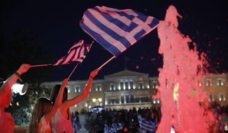 Young girls wave Greek flags as supporters of the No vote react after the first results of the referendum at Syntagma square in Athens, Sunday, July 5, 2015. Greece faced an uncharted future as its interior ministry predicted Sunday that more than 60 percent of voters in a hastily called referendum had rejected creditors' demands for more austerity in exchange for rescue loans. (AP Photo/Petros Giannakouris)