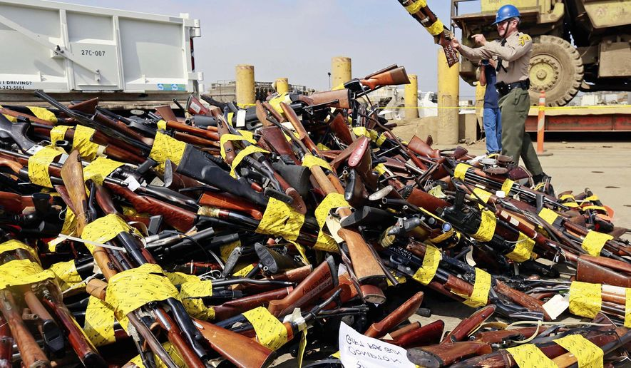A Los Angeles County Sheriff's deputy tosses weapons into a large pile prior to them being melted down as part of the annual Gun Melt at a steel mill in Rancho Cucamonga, Calif., Monday, July 6, 2015. The department melted down more than 3,400 weapons and firearms. (AP Photo/Nick Ut)