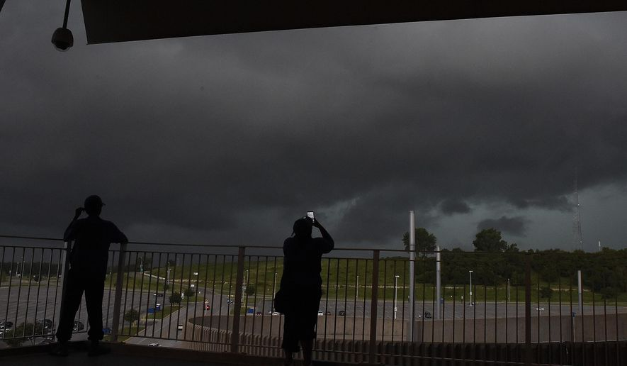 Workers watch as storm clouds approach Kauffman Stadium before the baseball game between the Kansas City Royals and Tampa Bay Rays on Monday, July 6, 2015, in Kansas City, Mo.  (John Sleezer/The Kansas City Star via AP) MANDATORY CREDIT