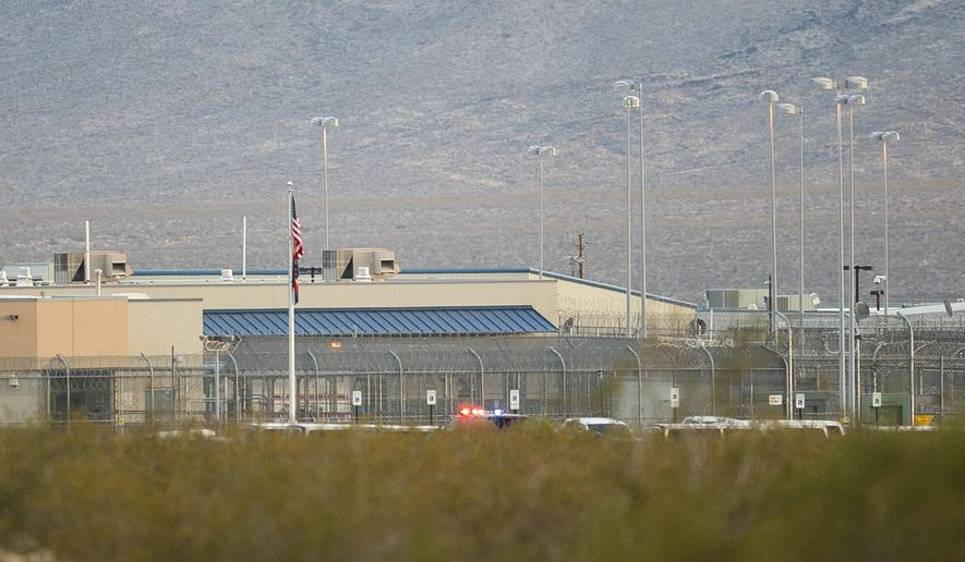 In a July 4, 2015 photo, police lights are seen in the distance after two-days of riots at Arizona State Prison-Kingman in Golden Valley, Ariz. State officials are relocating over 1,000 prisons from the privately run prison located about 15 miles west of Kingman because of damage from disturbances last week and over the weekend. (Patrick Breen/The Arizona Republic via AP) MARICOPA COUNTY OUT - NO MAGS- NO SALES - MANDATORY CREDIT